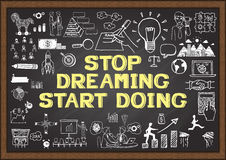 Inspirational quote. Stop dreaming start doing. wise saying on chalkboard with business doodles. Stock Image