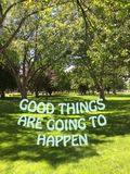 Inspirational quote on summer park landscape. Inspirational quote on scenic park landscape with green grass field and big trees on a sunny day. Good things are royalty free stock photography
