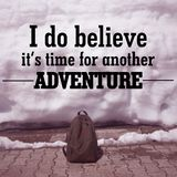 Inspirational Quote about travel. Inspirational Motivational Quote ` I do believe it`s time for another adventure` on blurred bag and snow background with Stock Image