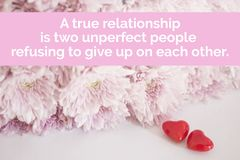 Inspirational quote `A true relationship is two un-perfect people refusing to give up on each other`. On blurred pink flowers background Stock Images
