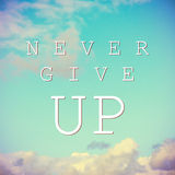 Inspirational quote on vintage sky background. Never give up Royalty Free Stock Photography