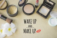 Inspirational quote `wake up and make up`. On blurred set of cosmetics background Stock Images