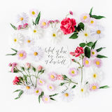 Inspirational quote `what is done in love is done well` written in calligraphy style on paper with pink, red roses, chamomiles and Royalty Free Stock Photography