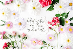 Inspirational quote `what is done in love is done well` written in calligraphy style on paper with pink, red roses, chamomiles and Royalty Free Stock Photos