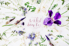 Inspirational quote `work hard dream big` written in calligraphy style on paper with wreath frame with purple iris flower and lili Royalty Free Stock Photo