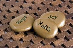 Inspirational Stones. Gold inspiration stones. Etched with the words Hope, Faith:, and Joy royalty free stock photos