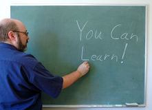 Inspirational teaching. Teacher writes an inspirational message on a chalkboard Royalty Free Stock Photo