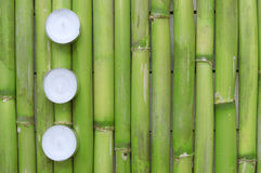 Inspirational zen background. Three candles aligned on a natural green bamboo background. Royalty Free Stock Image