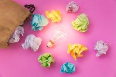 Inspirationskonzept mit zerknittertem Farbpapier und Glühlampe Stockfoto