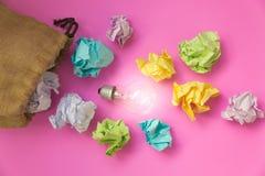 Inspirationskonzept mit zerknittertem Farbpapier und Glühlampe Stockfotos