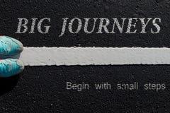 Inspirationszitat: Große Reisen fangen mit kleinen Schritten auf a an stockfoto