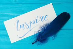 Inspire. Beautiful blue letters on canvas with blue feather. Calligraphy script. Art of writing letters. Background.  royalty free stock photos