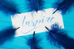 Inspire. Beautiful blue letters on canvas in feathers frame. Calligraphy script. Art of writing letters. Background stock image