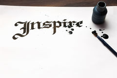 Inspire calligraphy . Artist workplace. Ink word on sheet of paper and pen top view. Drawing lessons, art school, creativity bacground concept royalty free stock images