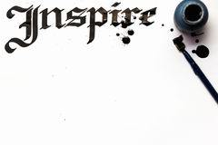 Inspire calligraphy lettering background. Word drawn with inks on sheet of paper. Drawing lessons, art school, creativity concept stock images