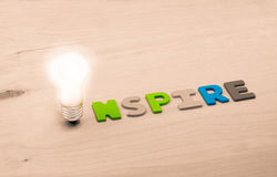 Inspire. The concept of inspire. Lamp and word inspire on a wooden background royalty free stock photo