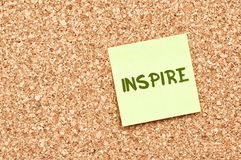 Inspire on Cork board with Note Paper. Inspire on Cork Board with yellow Sticky Note Paper royalty free stock photo