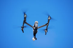 Inspire 1 Drone Flying Bottom View. Flying Inspire 1 drone closeup side view with a blue sky background royalty free stock image