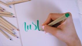 inspire El calígrafo escribe con palabra verde del marcador en el Libro Blanco calligraphy Fuente del ornamento El arte de las le almacen de video