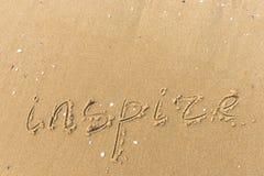 Inspire escrita en la arena de la playa fotos de archivo