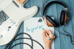 inspire Guss des Beschriftungswortes auf Weißbuch mit grüner Tinte durch Schreibkünstler Musikrahmen - Gitarre, Kopfhörer GR stockfoto