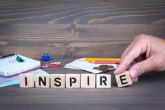inspire Hölzerne Buchstaben auf dunklem Hintergrund stockbilder