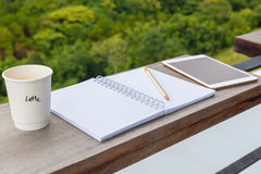 Inspire Outdoor Writing. Opened notebook with cup of coffee and tablet, prepare to write at the balcony by the forest view environment stock images