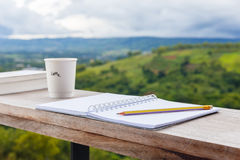 Inspire Outdoor Writing. Opened notebook with pencil and cup of coffee, prepare to write at the balcony by the mountain view environment royalty free stock image