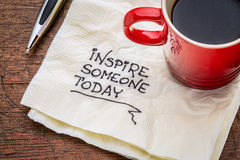 Inspire someone today. Motivational handwriting on a napkin with cup of coffee stock photo