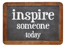 Inspire someone today. Motivational phrase on a vintage slate blackboard royalty free stock images