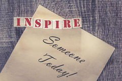 Inspire someone today quote. On a wooden background royalty free stock photo
