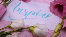 Inspire text. Font of lettering motivational word on white canvas with blue ink. Flowers eustoma frame on pink table