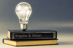 Inspire and vision. Light bulb glowing on the book of inspire and vision royalty free stock image