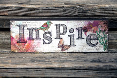 Inspire. A wall decor against a rustic wood background stock image