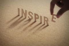 INSPIRE wood word on compressed board. With human`s finger at E letter stock photo