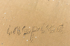 Inspire written on the beach sand Stock Photos