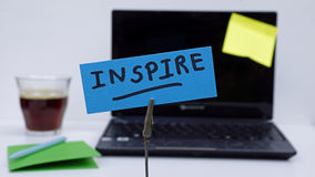 Inspire written. On a memo at the office Stock Images