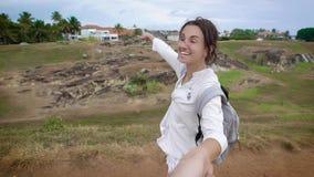 Inspired微笑的妇女拉扯她的摄制男朋友的手并且带领他的峭壁边缘在美丽如画的 股票录像