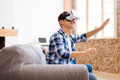 Inspired adolescent touching the imaginary picture. Amusement. Delighted well-built stylish adolescent smiling wearing a VR headset and sitting on the sofa and Stock Photo