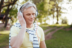Inspired aging man enjoying music outdoors. Full of inspiration . Involved smiling retired man using headphones while enjoying weather in the park and listening stock image