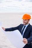 Inspired architect. Cheerful young man in formalwear and hardhat examining blueprint while standing in desert Royalty Free Stock Photography