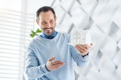 Inspired architect holding a model of a house. Smiling. Handsome content dark-haired bearded man smiling and holding a model of a future house and looking at it Stock Photo