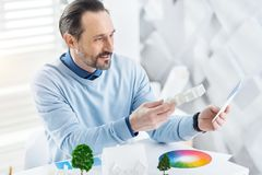 Inspired architect making plan of a future house. I love architecture. Handsome cheerful dark-haired bearded man smiling and holding a model of a future house Royalty Free Stock Photos