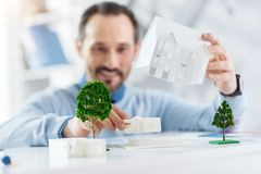 Inspired architect working on his project. I love constructing. Good-looking cheerful dark-haired bearded man smiling and holding a model of a future house while Royalty Free Stock Images