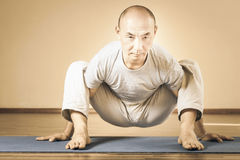 Inspired asian man doing exercise of yoga indoor Stock Photos