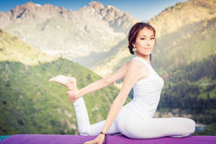 Inspired asian woman doing exercise of yoga at mountain Stock Images