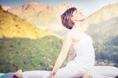 Inspired asian woman doing exercise of yoga at mountain range. Of Kazakhstan. She dressed in white sportswear Stock Image