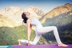 Inspired asian woman doing exercise of yoga at mountain range Royalty Free Stock Photography