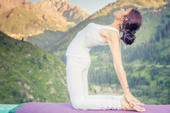 Inspired asian woman doing exercise of yoga at mountain range. Of Kazakhstan. She dressed in white sportswear Royalty Free Stock Image
