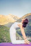 Inspired asian woman doing exercise of yoga at mountain range Stock Photography